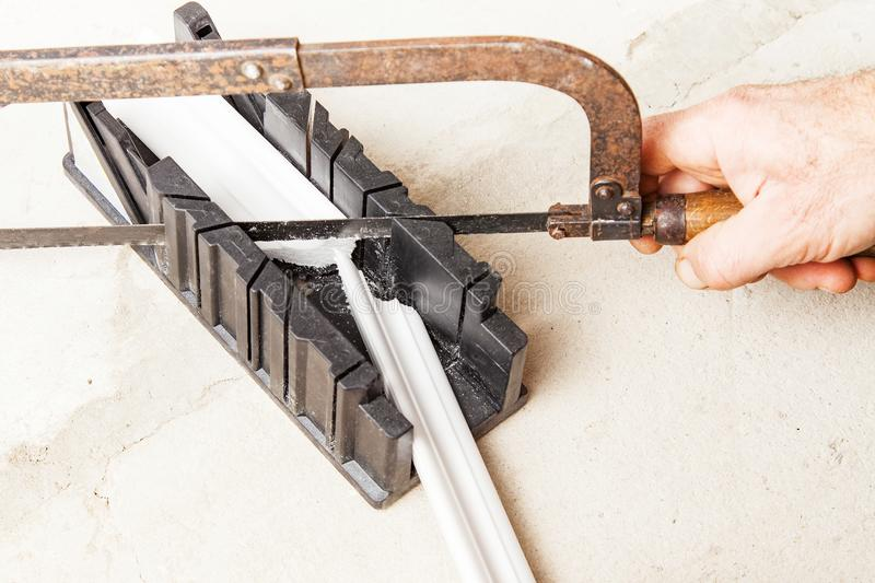 Cutting ceiling skirting in miter box. Cutting ceiling moldings in miter box closeup royalty free stock image