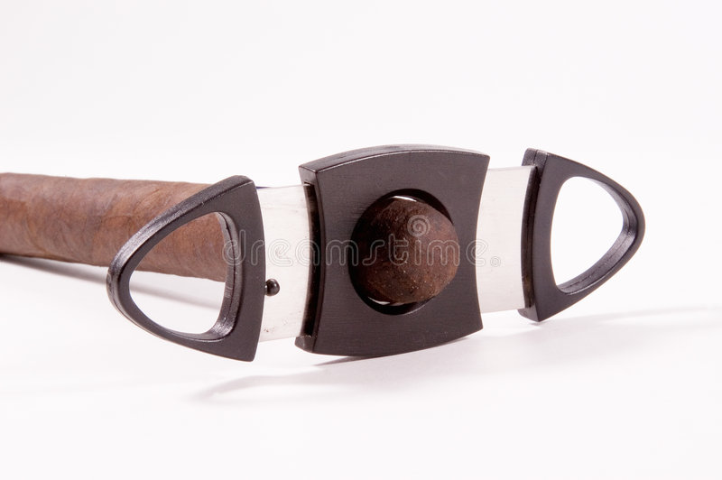 Cutting a Cigar. A cigar cutter with cigar in place to trim off end and perpare stogie for smoking stock image