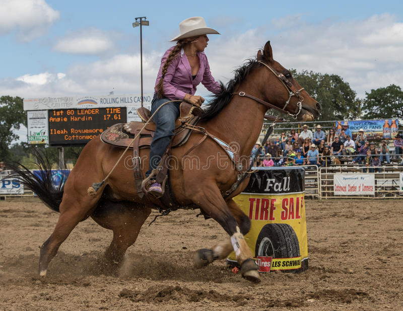 Cutting the Corner. A cowgirl clears a barrel and sprints home during a barrel racing event. The rodeo in Cottonwood, California is a popular event on Mother's stock photo