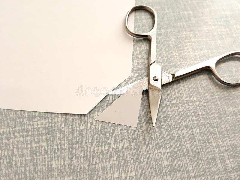 Cutting corners idiom. Briticism hand takes sheet of paper and cutting corners by scissors doing something so easily and cheaply as possible stock photography