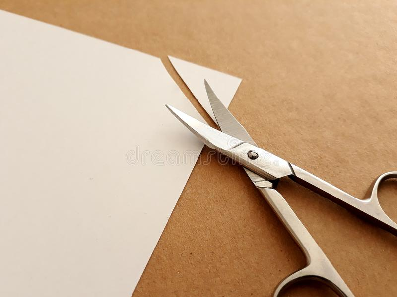 Cutting corners idiom. Briticism hand takes sheet of paper and cutting corners by scissors doing something so easily and cheaply as possible stock photo