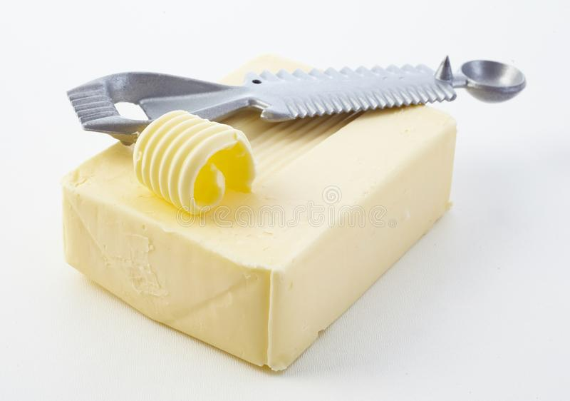 Cutting a curl off a pat of fresh butter stock photo