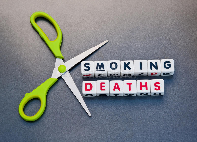 Cutting deaths from smoking. Green handled scissors against text ' smoking deaths ' in uppercase letters inscribed on small white cubes, gray background royalty free stock photos