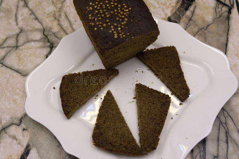 Cutting delicious homemade black bread. Borodinsky bread is a traditional Russian rye-wheat bread with maltose syrup, malt and cor royalty free stock photo