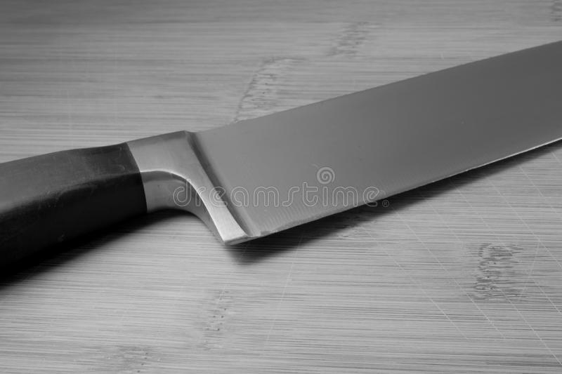 Monotone of a chefs knife on a bamboo cutting board royalty free stock photo