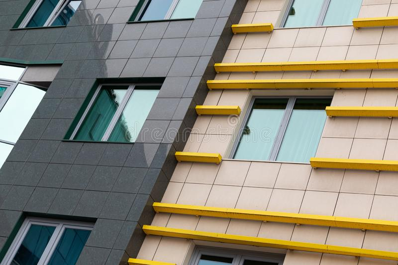 Cutting-edge tiled luxury apartment facade with beige and black ceramics, bright yellow details and wide windows.  royalty free stock photo