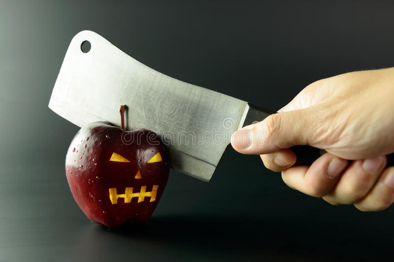 Cutting evil apple. With knife on black background stock photography