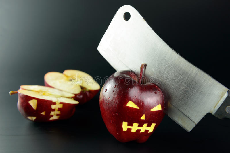 Cutting evil apple. With knife on black background royalty free stock photo