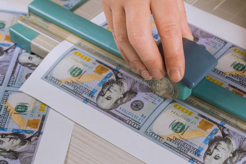 Cutting fake dollars cutter banknotes, fake money currency counterfeiting. Cutting fake US dollars cutter banknotes, fake money currency counterfeiting, crime royalty free stock photography