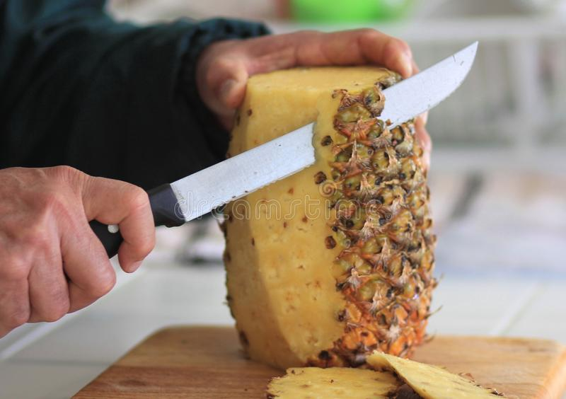 Cutting a fresh Pineapple. Cutting and cleaning a fresh pineapple on a wooden cutting board royalty free stock photo