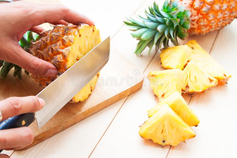 Cutting fresh pineapple on wooden table. Healthy and Diet concept royalty free stock image