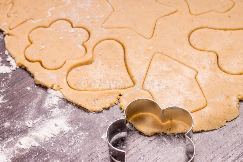 Cutting gingerbread cookies from rolled out dough royalty free stock photography
