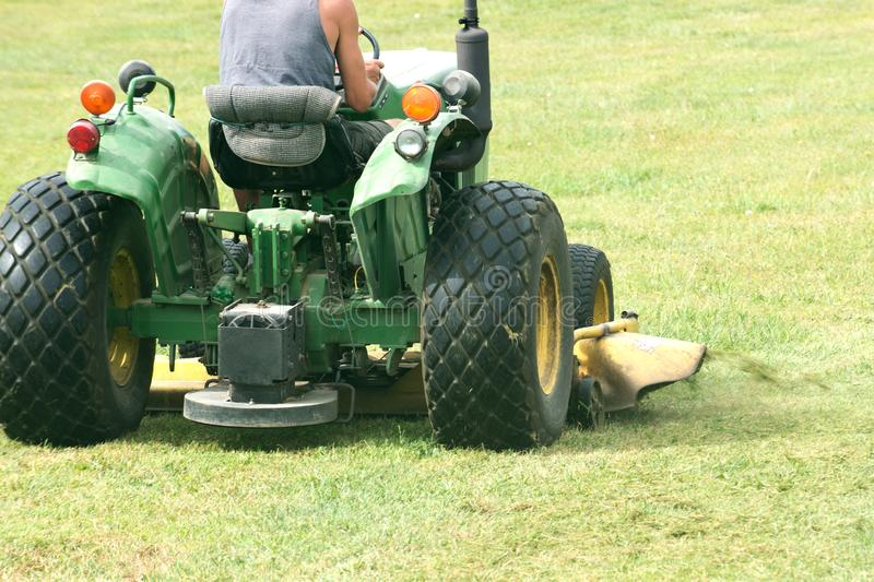 Commercial riding lawn mower. Cutting grass with commercial riding lawn mower royalty free stock image