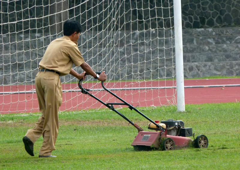 Cutting grass. Workers were cutting the grass in a stadium in the city of Solo, Central Java, Indonesia stock photo