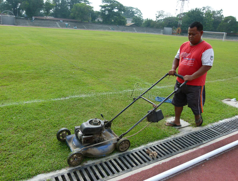 Cutting grass. Workers were cutting the grass in a stadium in the city of Solo, Central Java, Indonesia stock images