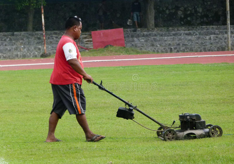 Cutting grass. Workers were cutting the grass in a stadium in the city of Solo, Central Java, Indonesia royalty free stock photos