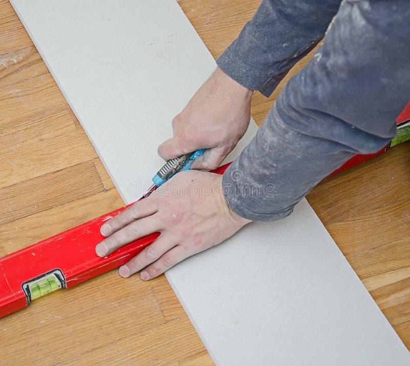 Cutting gypsum plasterboard royalty free stock photo