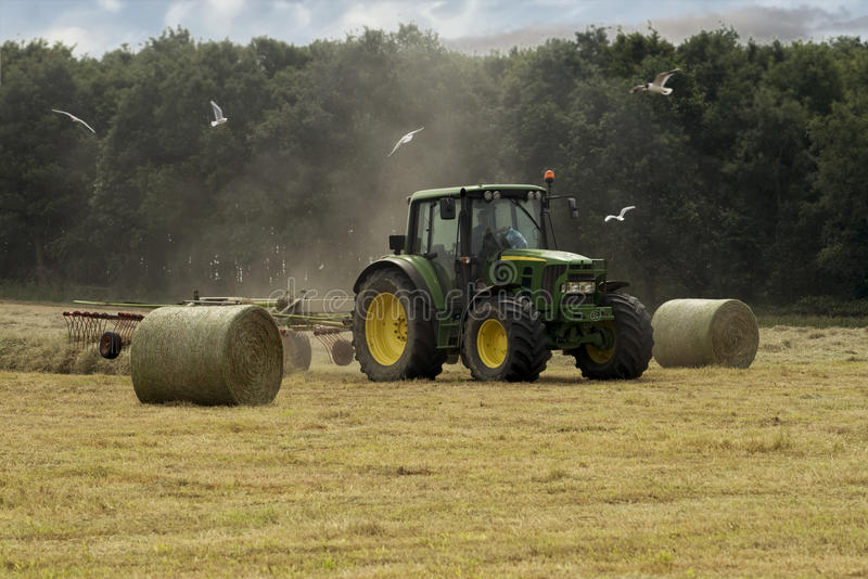 Cutting hay in the summertime. Cutting hay the tractor in the summertime royalty free stock photos
