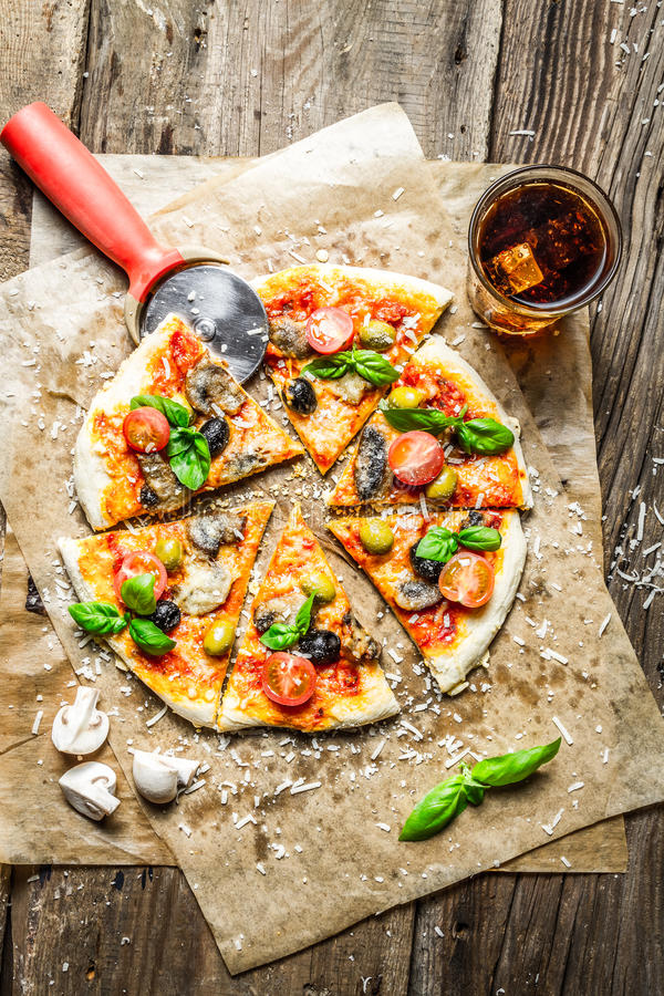 Cutting homemade pizza with basil stock image