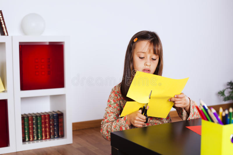 Cutting a house on a red paper. Little girl cutting a house on a red paper stock photo