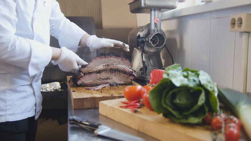 Cutting of a large piece of smoked meat on a wooden board royalty free stock photos