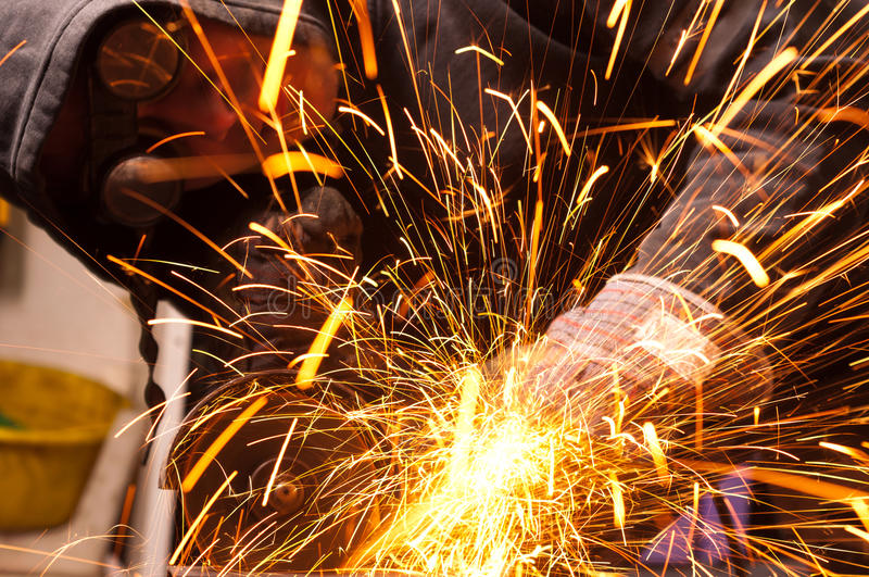 Cutting metal. Worker cutting metal with many sharp sparks stock image