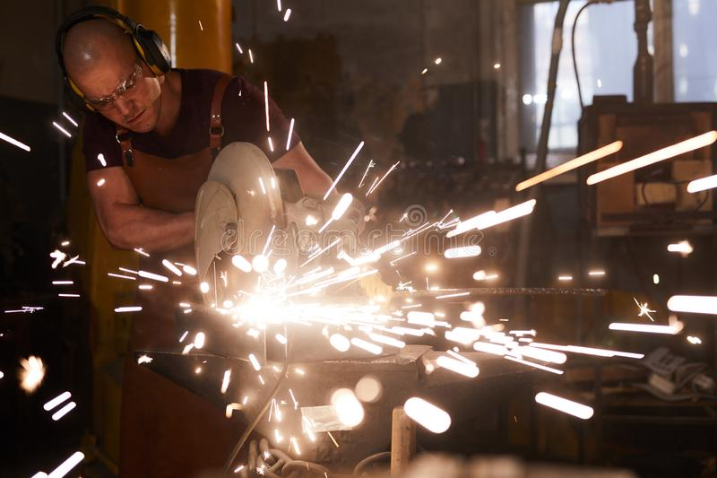 Cutting metal with circular saw. Serious busy bald metalworker in ear protectors standing by anvil and cutting metal with circular saw royalty free stock images