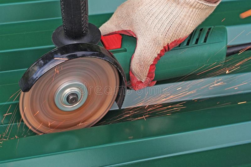 Cutting metal by electric wheel grinding. royalty free stock photography