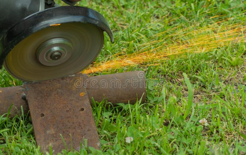 Cutting metal on grass with a hand tool. sparks flying from iron. selective focus. stock images