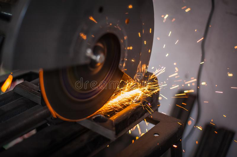 Cutting metal with grinder in workshop. Sparks while grinding iron. Cutting machine. Tool, worker, circular, steel, manufacturing, industry, equipment, disc stock image
