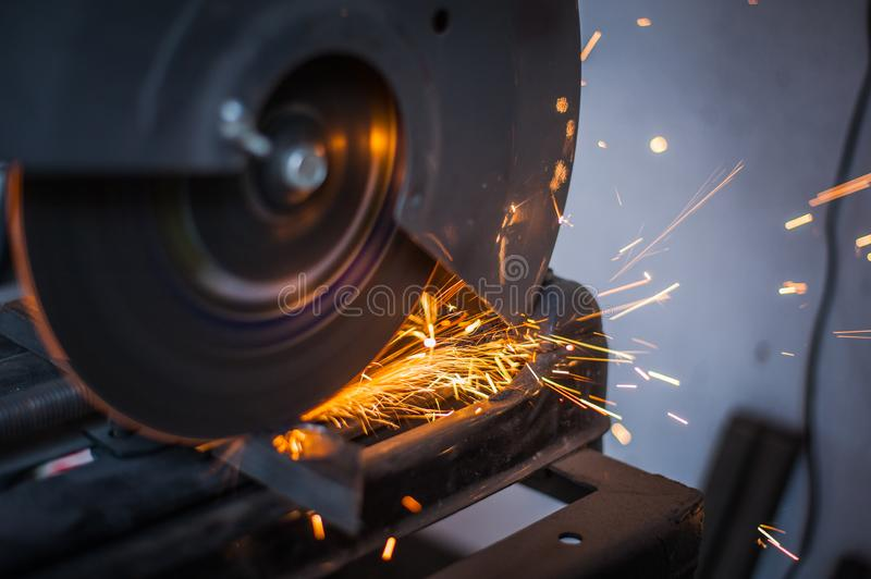 Cutting metal with grinder in workshop. Sparks while grinding iron. Cutting machine. Tool, worker, circular, steel, manufacturing, industry, equipment, disc stock photos