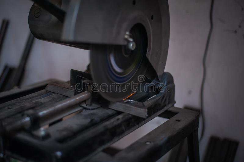 Cutting metal with grinder in workshop. Sparks while grinding iron. Cutting machine. Tool, worker, circular, steel, manufacturing, industry, equipment, disc royalty free stock images