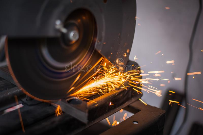 Cutting metal with grinder in workshop. Sparks while grinding iron. Cutting machine. Tool, worker, circular, steel, manufacturing, industry, equipment, disc stock images