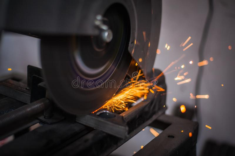 Cutting metal with grinder in workshop. Sparks while grinding iron. Cutting machine. Tool, worker, circular, steel, manufacturing, industry, equipment, disc royalty free stock photo