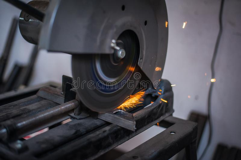Cutting metal with grinder in workshop. Sparks while grinding iron. Cutting machine. Tool, worker, circular, steel, manufacturing, industry, equipment, disc stock photo