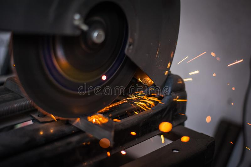 Cutting metal with grinder in workshop. Sparks while grinding iron. Cutting machine. Tool, worker, circular, steel, manufacturing, industry, equipment, disc royalty free stock image