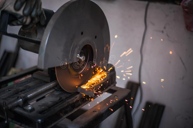 Cutting metal with grinder in workshop. Sparks while grinding iron. Cutting machine. Tool, worker, circular, steel, manufacturing, industry, equipment, disc royalty free stock photos