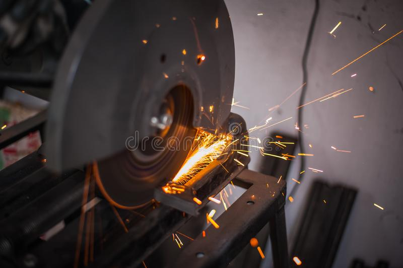 Cutting metal with grinder in workshop. Sparks while grinding iron. Cutting machine. Tool, worker, circular, steel, manufacturing, industry, equipment, disc royalty free stock photography