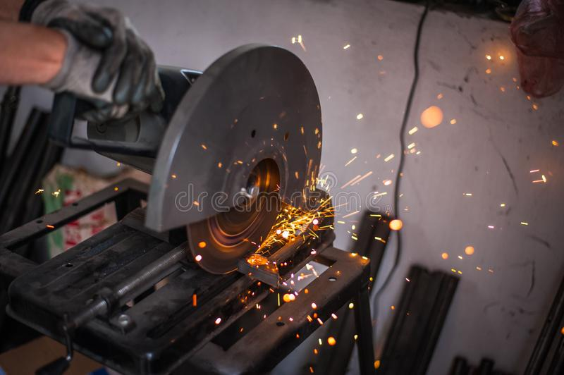 Cutting metal with grinder in workshop. Sparks while grinding iron. Cutting machine. Tool, worker, circular, steel, manufacturing, industry, equipment, disc stock photography