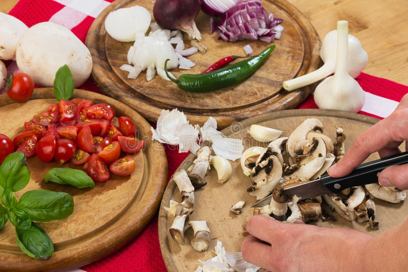 Cutting mushrooms and vegetables royalty free stock image