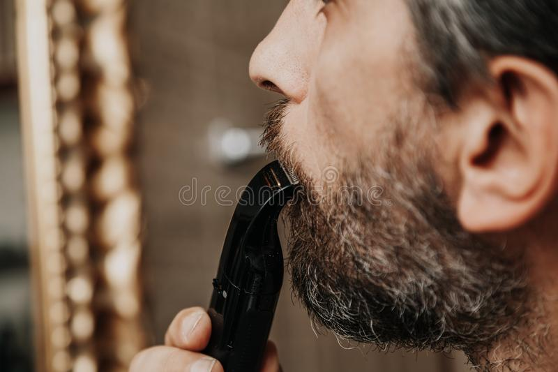 Cutting mustache with black trimmer close-up. Haircut beard trimmer. A man cuts his mustache with a machine stock photography