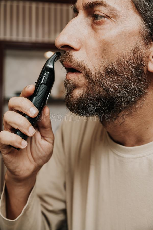Cutting mustache with black trimmer close-up. Haircut beard trimmer. A man cuts his mustache with a machine stock images