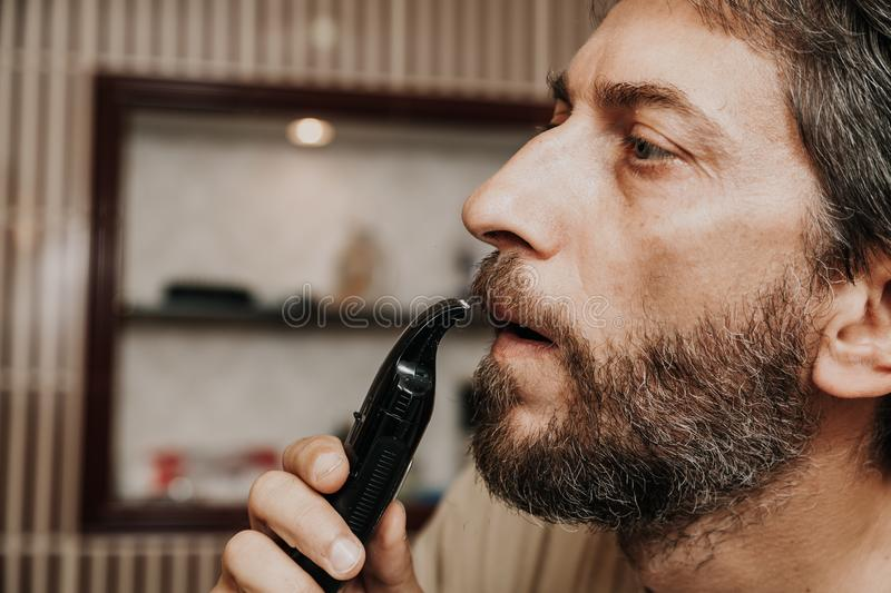 Cutting mustache with black trimmer close-up. Haircut beard trimmer. A man cuts his mustache with a machine royalty free stock photo