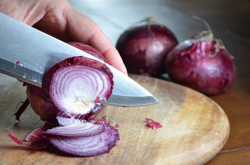 Cutting onions with knife on cutting board royalty free stock photography