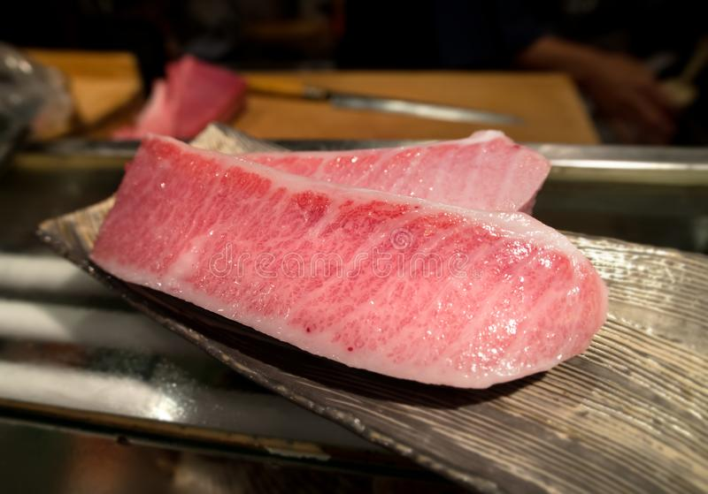 Cutting of otoro from blue fin tuna for sashimi. royalty free stock images