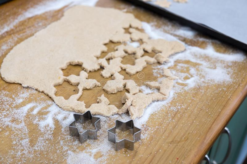 Cutting out star shaped cinnamon Christmas cookies with biscuit royalty free stock photos