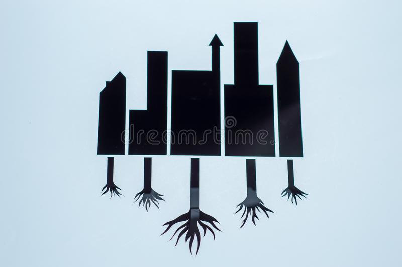 Cutting paper illustration save earth. black building with root of trees stock image