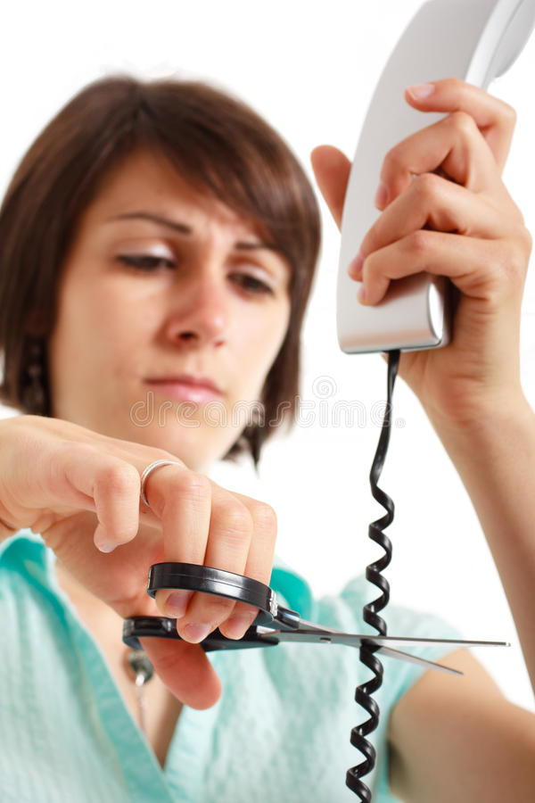 Cutting phone cable. Portrait of a stressed woman cutting a telephone cable stock photo