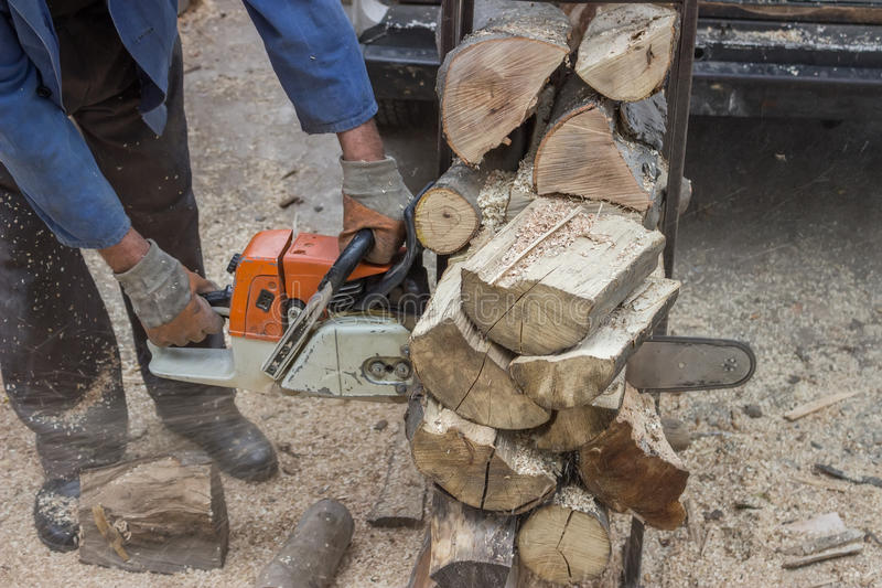Cutting pile of wood with a chainsaw. Winter preparation stock images