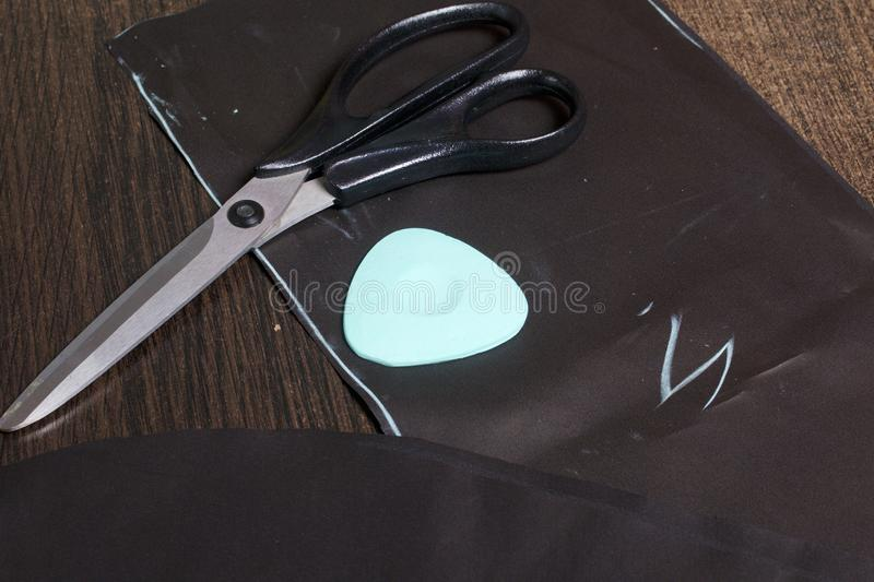 Cutting of the product for sewing. On the table is a cloth with chalk-marked garments. Just lie scissors and chalk. Cutting of the product for sewing. On the royalty free stock photos